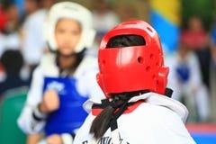 Девушка воюя на этапе во время состязания Тхэквондо Стоковая Фотография