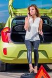 Девушка водителя вызывая механика стоя около автомобиля Стоковая Фотография RF