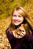 девушка вручает ей желтый цвет листьев довольно Стоковые Изображения RF