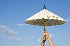 Руки девушки держа бумажный зонтик Стоковые Фото