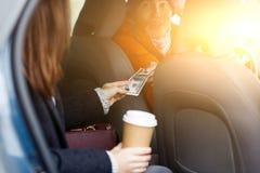 Девушка врученная над деньгами водителя для перемещения, сидя в такси Стоковое Изображение