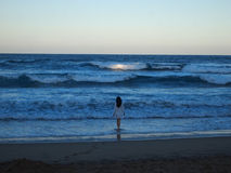 Девушка входя в океан на заход солнца Стоковая Фотография RF