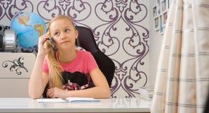 Девушка выбирает вверх телефон и домашняя работа делать Стоковое Фото