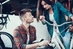 Девушка выбирает велосипед города с другом в магазине спорта стоковое изображение rf