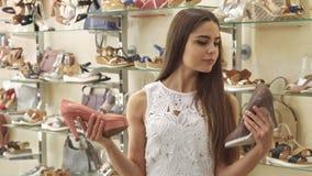 Девушка выбирает между персиком и коричневыми ботинками стоковое фото rf