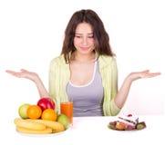 Девушка выбирает между плодоовощ и помадками стоковое изображение rf