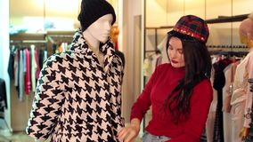 Девушка выбирает одежды в магазине, она выбирает пальто осени черно-белое видеоматериал
