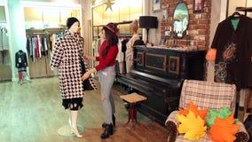 Девушка выбирает одежды в магазине, она выбирает пальто осени черно-белое сток-видео