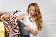 Девушка выбирает одежды в магазине одежды стоковое изображение rf