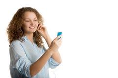 Девушка выбирает песню на ее игроке Стоковая Фотография