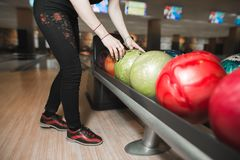 Девушка выбирает покрашенный шар для того чтобы сыграть боулинг перед бросать причаливая штыри игры боулинга шарика Стоковое Фото