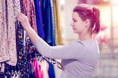 Девушка выбирает рубашку в магазине модной одежды Брюнет в магазине одежды bigtime детеныши покупкы девушки Стоковые Фото