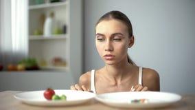 Девушка выбирая между овощами и таблетками, здоровым питанием против лекарств потери веса стоковые фото