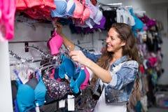 Девушка выбирая нижнее белье на магазине Стоковые Фото