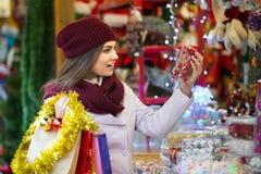 Девушка выбирая украшение рождества на рынке Стоковые Изображения RF