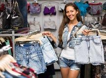 Девушка выбирая шорты в магазине одежды Стоковые Фото