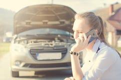Девушка вызывать Сломленный автомобиль на предпосылке Женщина сидит на колесе Сексуальный ремонт молодой женщины автомобиль Естес Стоковая Фотография