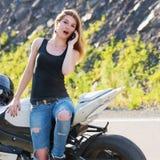Девушка вызывая на телефоне около мотоцикла стоковые изображения rf