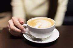Девушка выпивает кофе в кафе Малая глубина поля Стоковые Изображения RF