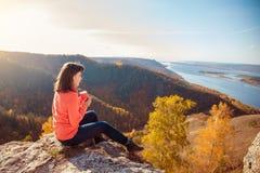 Девушка выпивает чай na górze горы Стоковое Фото