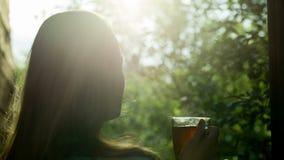 Девушка выпивая горячий чай внешний на заходе солнца видеоматериал