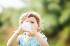 Девушка выпивая от пластичной бутылки Стоковая Фотография RF