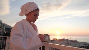 Девушка выпивая от чашки на балконе видеоматериал