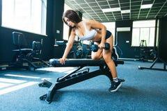 Девушка выполняет гантель с одной рукой в наклоне используя стенд тренировка на самых широких задних мышцах с стоковые изображения rf