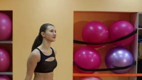 Девушка выполняет шаг cardio с гантелями в спортзале сток-видео