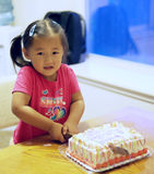 девушка вырезывания именниного пирога стоковое изображение rf