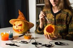 Девушка высекает тыкву на хеллоуин дома Стоковая Фотография