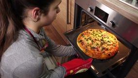 Девушка вытягивает вне горячую пиццу от печи сток-видео