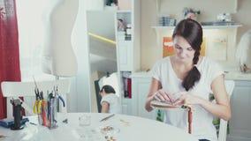 Девушка вышивает используя декоративные камни и обручи сток-видео