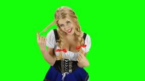 Девушка в баварском костюме flirting с кто-то Экран зеленого цвета Oktoberfest сток-видео
