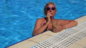 Девушка в бассейне выпивая коктеиль сток-видео