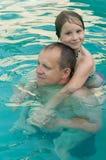 Девушка в бассейне смотря в камеру и обнимая отца от задней части Стоковое Изображение