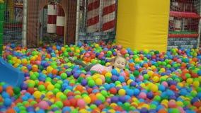 Девушка в бассейне шариков видеоматериал