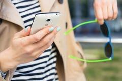 Девушка в бежевой куртке и striped рубашке держа мобильный телефон Стоковые Фото
