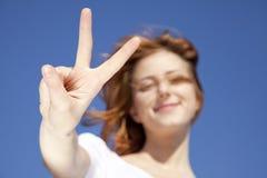 Девушка в белизне которые показывают символ руки v. стоковое изображение