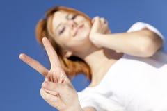 Девушка в белизне которые показывают символ руки v. стоковые изображения