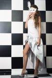 Девушка в белой маске на предпосылке шахматной доски Стоковое Изображение