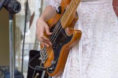 Девушка в белом платье играя электрическую басовую гитару стоковые фото