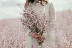 Девушка в белом платье с цветками шалфея в руках, на предпосылке мудрого поля стоковое фото