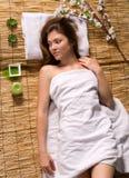 Девушка в белом полотенце лежа на обработках спы Стоковое фото RF