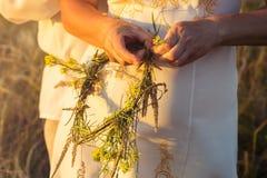 Девушка в белом традиционном славянском платье wreathes венок свежих wildflowers на заходе солнца Русские традиции стоковые изображения rf