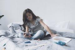 Девушка в белых наушниках сидит на кровати и слушает к музыке на сером smartphone Стоковые Фотографии RF