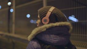 Девушка в беспроводных наушниках, идет к городу ночи сток-видео