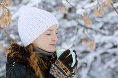 Девушка в белой шляпе с чашкой чаю среди покрытых снег ветвей дерева, взглядом со стороны Стоковые Фотографии RF