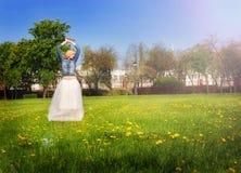 Девушка в белой юбке и куртке джинсовой ткани наслаждаясь солнечным днем Стоковое фото RF