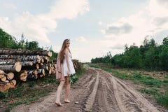 Девушка в белом платье в деревне идет на дорогу Стоковое фото RF